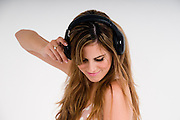 Female teen dances while she enjoys music on her headphones on white background