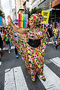 New York, NY - 25 June 2017. New York City Heritage of Pride March filled Fifth Avenue for hours with groups from the LGBT community and it's supporters. A marcher in a colorful dress in a fabric printed with colorful tropical fruits.