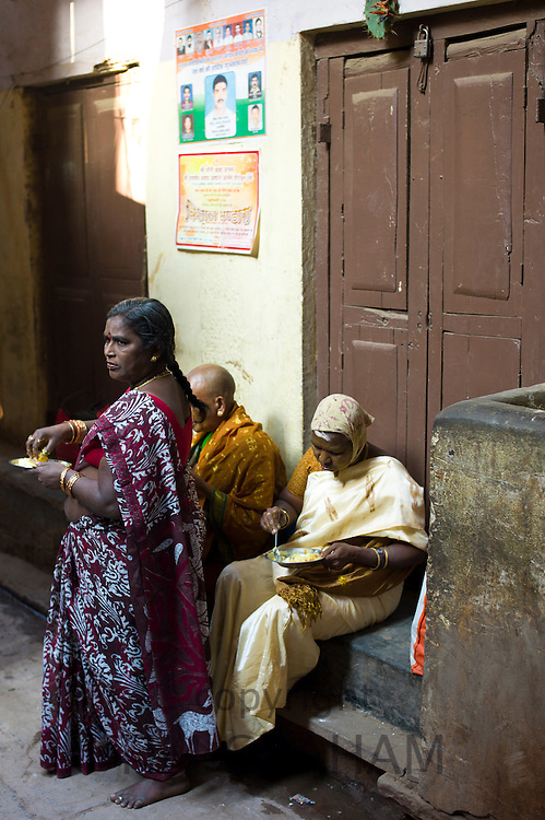 Indian people having lunch in an alleyway in the holy city of Varanasi, Benares, Northern India