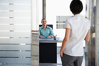 Man talking to woman standing in doorway of his office