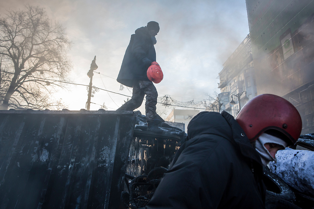 KIEV, UKRAINE - JANUARY 24: Anti-government protesters climb on top of burned-out buses near Dynamo Stadium on January 24, 2014 in Kiev, Ukraine. After two months of primarily peaceful anti-government protests in the city center, new laws meant to end the protest movement have sparked violent clashes in recent days. (Photo by Brendan Hoffman/Getty Images) *** Local Caption ***