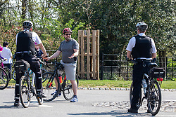 © Licensed to London News Pictures. 11/04/2020. London, UK. Two Police cyclists patrolling Richmond Park question a cyclist where a cycling ban is in place for adults in the park during the coronavirus disease pandemic. Londoners have been told to stay at home and only leave homes to exercise or when absolutely essential in an attempt to fight the spread of COVID-19 as temperatures for the Easter Bank holiday weekend are expected to reach 26c. Photo credit: Alex Lentati/LNP