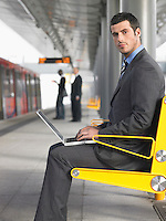 Businessman sitting on bench working on laptop at Train Station side view