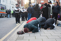 "Mayfair, London, November 28th 2014. A protest against Egypt's leader Al-Sisi descended into moinor scuffles as right wing ""patriots"" from anti-Islamic group Britain First arrived to protest against the presence of Islamist preacher Anjem Choudary, who was recently arrestred as part of an ant-terror operation. Playing patriotic British Music, Britain First accused Muslims of worshiping a ""devil"" and a ""paedophile prophet"". Police had to intervene before hotheads on both sides became violent. PICTURED: Anjem Choudary, centre, prays as behind him demonstrations and counter-demonstrations continue."