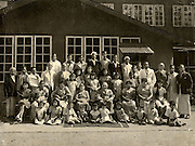 """Nawalapitiya. probably 1934. Queensberry factory<br /> 2 people seated in the middle are mr and mrs McNeil who was the estate superintendent  The other white guy in specs is Mr Smith the dispenser. Far right corner in the checked sarong and coat in mr Babasinghe who owned the corner shop on the estate. He did not have one hand.""""<br />  My mum in law's family was pretty small, they had 14 kids and most of them are there in this image"""