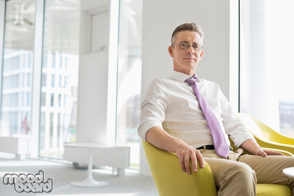 Portrait of confident businessman sitting at office lobby