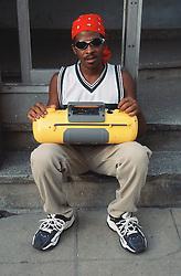 Young man sitting on street in Havana holding large yellow ghetto blaster radio,