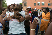 Two bystanders embrace near 500 Genesee Street in Rochester on Thursday, August 20, 2015. Three were fatally shot and another four injured in a drive-by shooting in front of the Boys and Girls Club of Rochester the night before.