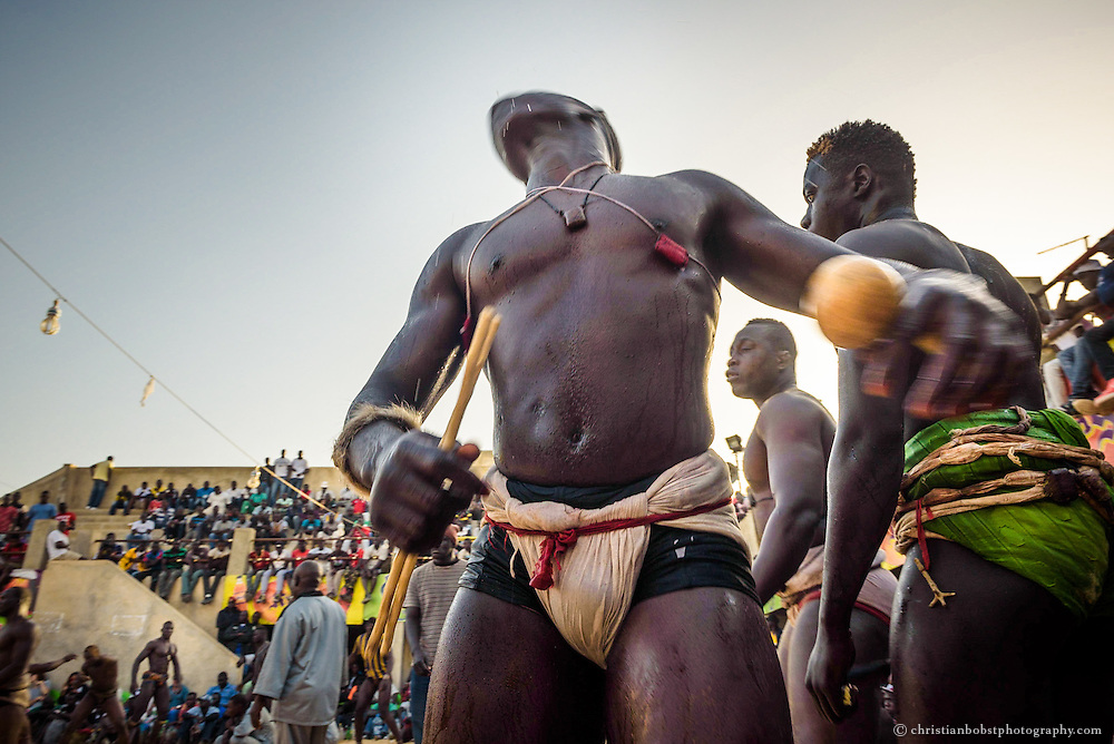 A Wrestler presents his Gris-gris amulets to the audience  before the fight in the Adrien Senghor arena begins, March 28, 2015;  To drumbeats and repetitive songs he dances himself into trance.