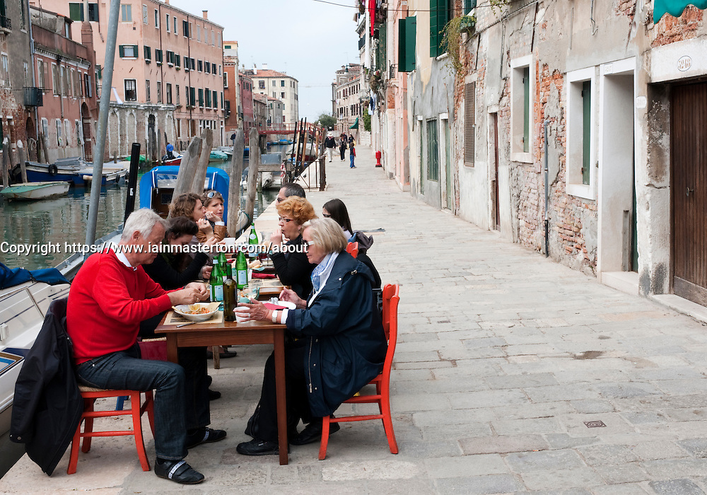 Small pavement restaurant beside canal in Cannaregio district of Venice Italy