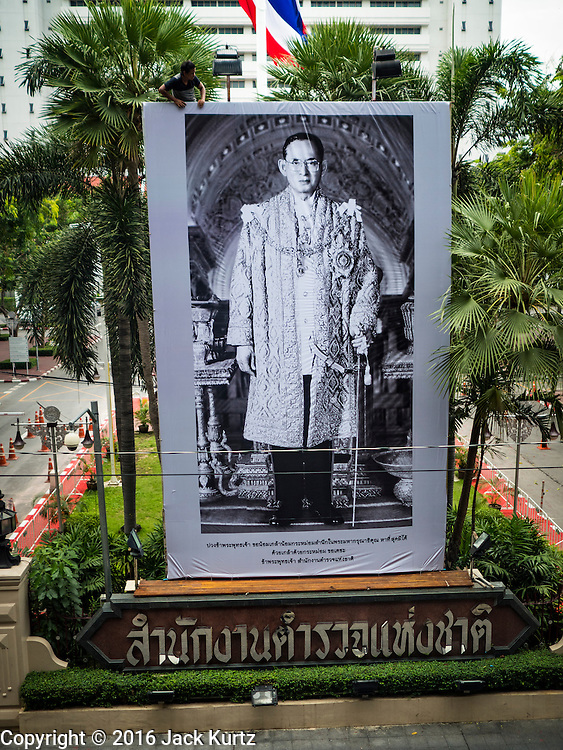 15 OCTOBER 2016 - BANGKOK, THAILAND:  A worker at Thai police headquarters hangs a black and white mourning portrait of Bhumibol Adulyadej, the King of Thailand. King Bhumibol Adulyadej died Oct. 13, 2016. He was 88. His death comes after a period of failing health. With the king's death, the world's longest-reigning monarch is Queen Elizabeth II, who ascended to the British throne in 1952. Bhumibol Adulyadej, was born in Cambridge, MA, on 5 December 1927. He was the ninth monarch of Thailand from the Chakri Dynasty and is known as Rama IX. He became King on June 9, 1946 and served as King of Thailand for 70 years, 126 days. He was, at the time of his death, the world's longest-serving head of state and the longest-reigning monarch in Thai history.     PHOTO BY JACK KURTZ