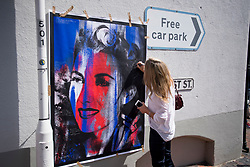 © Licensed to London News Pictures. 10/07/2020. London, UK. A woman signs a large picture of  Dame Vera Lynn, in the town of Ditchling, East Sussex, ahead of the funeral. The 'Forces' Sweetheart', who died last month aged 103, was famous for singing performances during WW2, which helped raise morale amongst troops abroad. Photo credit: Ben Cawthra/LNP