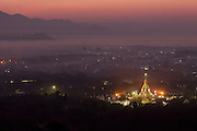Kuthodaw Pagoda from Mandalay Hill at sunrise, mountains in background with smoke, mist and lights of the city
