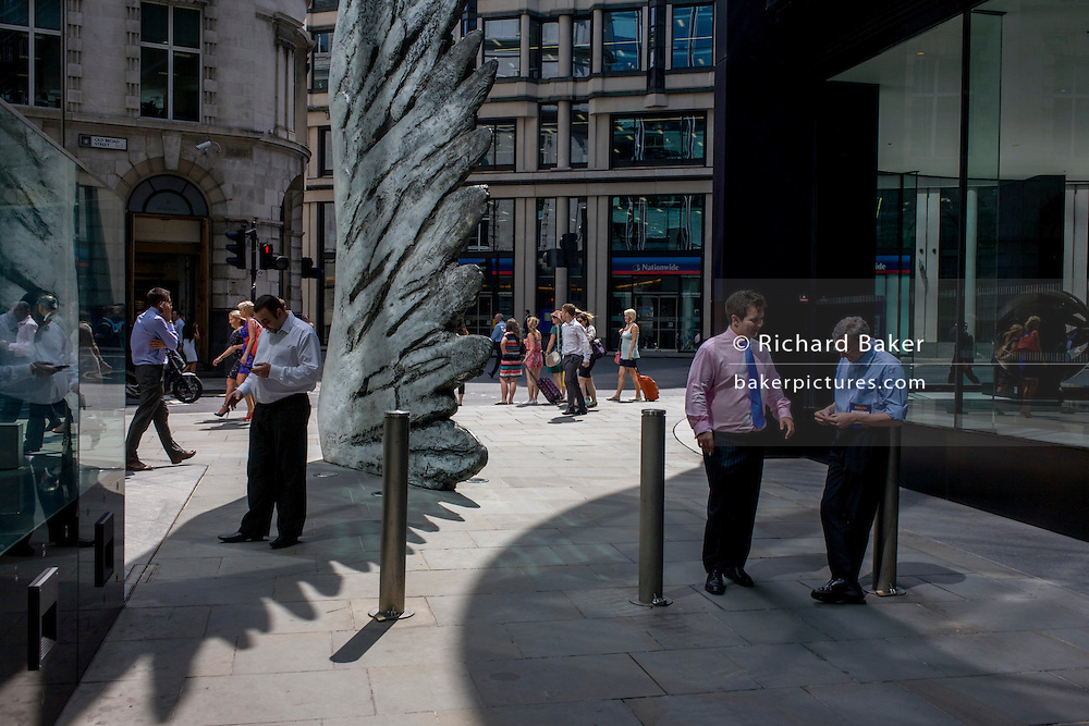 City workers smoke cigarettes by the giant artwork of a bronze wing during a spring lunchtime in London's financial district. As light reflects off nearby office buildings, the lunchtime crowd walk past this giant artwork on their way to meetings and sandwich bars. The ten-metre-tall bronze sculpture is by President of the Royal Academy of Arts, Christopher Le Brun, commissioned by Hammerson in 2009. It is called 'The City Wing' and has been cast by Morris Singer Art Founders, reputedly the oldest fine art foundry in the world.