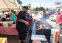 Mike Joslin serves up burgers and hot dogs at Sanborn's Auto Repair on Saturday during Lucky Jr's birthday party.  (Karen Bobotas/for the Laconia Daily Sun)