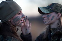 FEMALE DEER HUNTER APPLYING FACE PAINT TO ANOTHER HUNTER