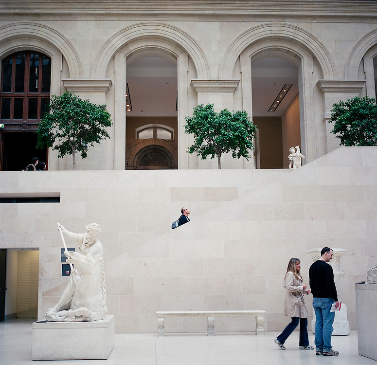 A tourist looks over a sculpture garden at the Louvre Museum during a visit in Paris, France.<br /> <br /> NOTE: Larger resolution versions of these images are available on request.