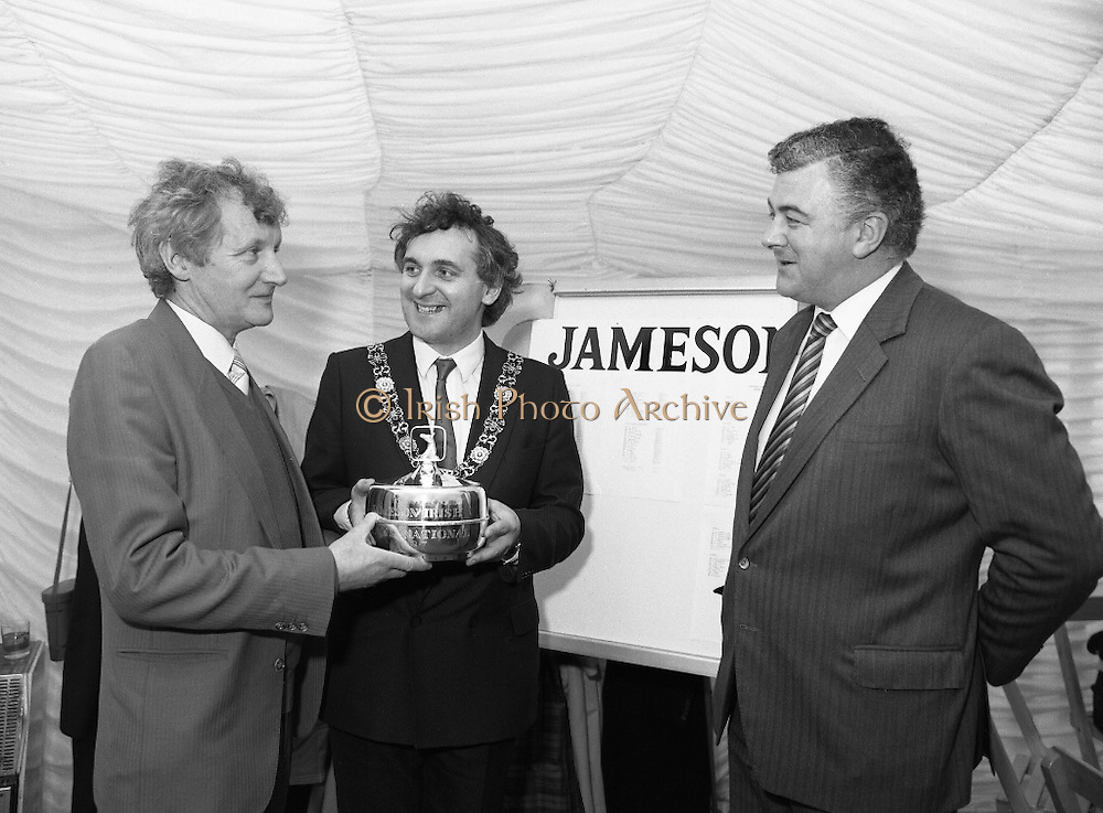 Irish Grand National At Fairyhouse.  (R54)..1987..20.04.1987..04.20.1987..20th April 1987..The Easter Racing Festival at Fairyhouse included the running of the Jameson sponsored Irish Grand National. Another featured race was the Jameson Gold Cup which was also run on Easter Monday...Mr John Glynn, owner of 'Brittany Boy,accepts the Jameson Irish Grand National Trophy from the Lord Mayor of Dublin, Mr Bertie Ahern. Jameson, Group, Managing, Directors  Mrs Richards Burrows, Jameson's, Irish, Whiskey, jameson,