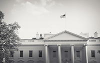 Two men stand on the roof of the White House, one with binoculars, Washington, DC, USA.