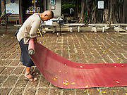 30 JULY 2016 - BANGKOK, THAILAND:  A man who lives in the Pom Mahakan Fort rolls up rattan mats. Residents of the slum have been told they must leave the fort and that their community will be torn down. Mahakan Fort was built in 1783 during the reign of Siamese King Rama I. It was one of 14 fortresses designed to protect Bangkok from foreign invaders. Only of two are remaining, the others have been torn down. A community developed in the fort when people started building houses and moving into it during the reign of King Rama V (1868-1910). The land was expropriated by Bangkok city government in 1992, but the people living in the fort refused to move. In 2004 courts ruled against the residents and said the city could take the land. Eviction notices have been posted in the community and people given until April 30 to leave, but most residents have refused to move. Residents think Bangkok city officials will start evictions around August 15, but there has not been any official word from the city.     PHOTO BY JACK KURTZ