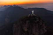 Christ the Redeemer statue on Corcovado Mountain looking toward the mountains at sunset in Rio de Janeiro, Brazil.