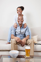 Portrait of excited young African American couple watching TV