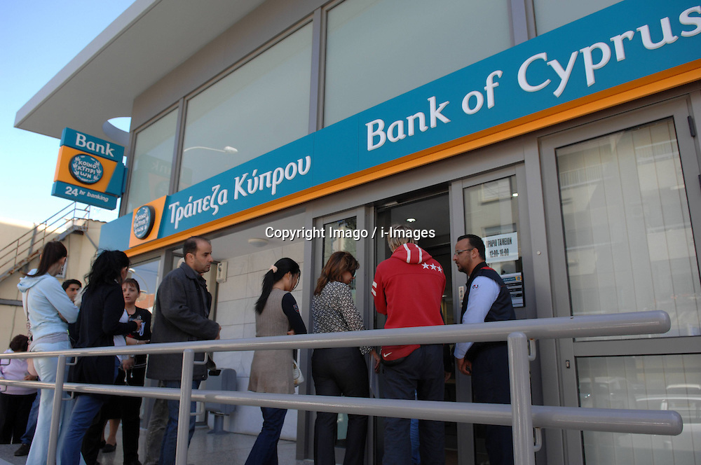 People wait outside a branch of Bank of Cyprus  before the reopening of the bank in Nicosia, capital of Cyprus, on March 28, 2013. Surprisingly few lined up outside banks in Cyprus when they reopened for business at noon on Thursday -- to the relief of authorities which have feared a run on the banks following a closure since March 16. Strict limits on bank transactions have been announced by the Central Bank and the ministry of finance in a bid to prevent a massive outflow of cash. A Central Bank official said banks would be open for transactions between 12:00 noon and 18:00 local time (10:00 GMT and 16:00 GMT), instead of the normal 08:30 to 13:00 local time bank hours. The decree imposing controls on bank transaction limits cash withdrawal to 300 euros per day per bank account and entirely prohibits payment by check. However, credit card holders can use them for commercial transactions for unlimited amounts of money., Nicosia, Cyprus, March 28, 2013. Photo by Imago / i-Images...UK ONLY.