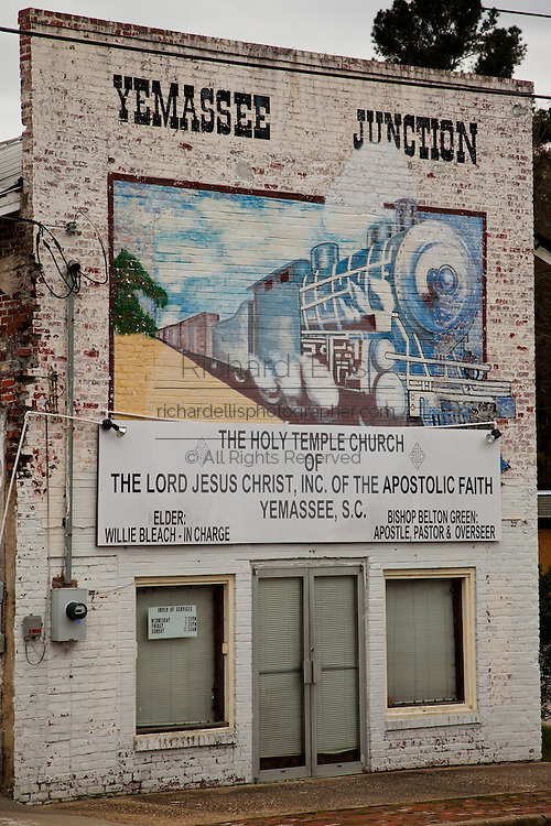 Southern style building with a mural marking the Yamassee Junction, the transfer rail station point for thousands of Marines during World War II, Korea & Vietnam. The building is now a store front apostolic faith church. .