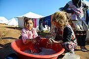 Two Syrian girls wash clothes outside their tent in the displaced persons camp in Atmeh, Syria. A third girl stands behind them.