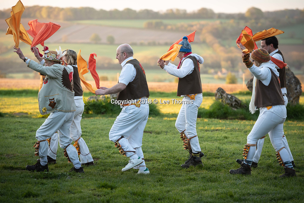 Rollright Stones, Nr Long Compton, Oxfordshire / Warwickshire, UK. 1st May 2018.  Members of the Owlswick Morris side entertain spectators at sunrise with traditional dancing at the historic Rollright Stones to celebrate the 1st May.  The Rollright Stones is a complex comprising of three Neolithic and Bronze Age megalithic monuments near the village of Long Compton, on the borders of Oxfordshire and Warwickshire. Made from local oolitic limestone, the three monuments now known as the King's Men and the Whispering Knights in Oxfordshire and the King Stone in Warwickshire, were built at separate periods in late prehistory.  Pictured: The Owlswick Morris side dance outside the King's Men Rollright Stones. // Lee Thomas, Tel. 07784142973. Email: leepthomas@gmail.com  www.leept.co.uk (0000635435)