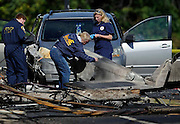 Investigators look at the remains of a small plane along Main St, Wednesday, Oct. 12, 2016, in East Hartford, Conn., a day following the plane's crash. The FBI is taking over as lead investigator in the deadly crash of a small plane carrying a flight instructor and a student pilot because of indications that it might have been a criminal act, safety officials said Wednesday. (AP Photo/Jessica Hill)