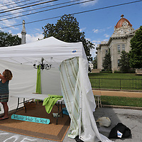 Barbara Eaton begin taking down the portective wall following Friday morning rain so she can begin filling her tent with her art fot this weekend's annual Gumtree Festival.