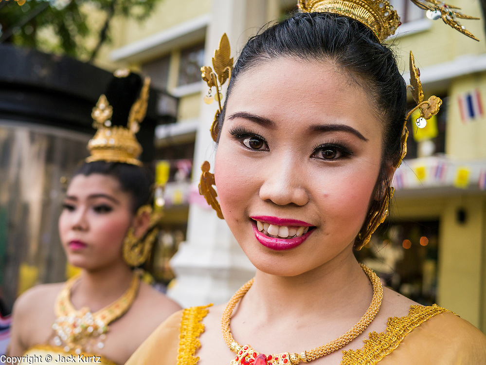 05 DECEMBER 2012 - BANGKOK, THAILAND:  Women prepare to parade to the Grand Palace during the public ceremony to celebrate the birthday of Bhumibol Adulyadej, the King of Thailand, on Sanam Luang, a vast public space in front of the Grand Palace in Bangkok Wednesday night. The King celebrated his 85th birthday Wednesday and hundreds of thousands of Thais attended the day long celebration around the Grand Palace and the Royal Plaza, north of the Palace. The Thai monarch is revered by most Thais as unifying force in Thailand's society, which is not yet recovered from the political violence of 2010.     PHOTO BY JACK KURTZ