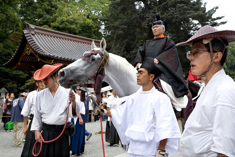 The head priest of the shrine riding one of the horses that will later be used for the Yabusame ritual, at the religious procession with portable shrines, during the second day of the 3-day anual festival of Tsurugaoka Hachimangu Shrine in Kamakura.
