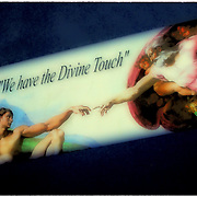 "Polariod transfer of moving company logo on side of truck ""We Have the Divine Touch"" from Michelangelo's Sistine Chapel ceiling ofn the hand of god giving life to Adam"