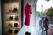 SHOT 9/23/2007 - Arsen Semenov, 27 (left) and Zema Alieva, 22 (right) walk past a dress and handbags on display in the front window of the Christian Dior store at Hopkins Ave. and Galena St. in Aspen, Co. on Sunday September 23, 2007. The store is just one of many of the high end luxury stores found in the mountain town that has become known as a playground for the rich and famous. Designer labels such as Prada, Bulgari and Gucci all have locations in Aspen. Semenov and Alieva both are originally from Russia but live now in Aspen.The city emerged as a skiing mecca following World War II and the foundation of the Aspen Skiing Company by Walter Paepcke, a Chicago industrialist who sought to create a utopian community of the mind and body. This historic character of the city has been challenged in recent decades by skyrocketing property values and the proliferation of second homes, increasingly shutting low- and middle-income workers out of the city and creating a large pool of commuters from nearby bedroom communities such as Basalt and Carbondale. At the same time, in stark contrast to its historic character, the city has emerged into international fame as a glitzy playground of the wealthy and famous..(Photo by Marc Piscotty / © 2007)