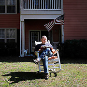 """Rich Page, of Beaufort, relaxes in the sun while reading a book in a rocking chair he moved from inside his apartment at The Oaks at Broad River Landing on February 20, 2014.  """"This is what I signed up for,"""" said Page."""