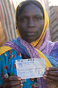 (MODEL RELEASED IMAGE). The Breidjing Refugee Camp, Eastern Chad on the Sudanese border shelters 30,000 people who have fled their homes in Darfur, Sudan. Here, D'jimia Ishakh Souleymane, 40 (and a widowed mother of 5), shows her UN ration food card. Food distribution for the Breidjing Refugee Camp in eastern Chad, run by the U.N. World Food Programme, is very systematic. Following a precise schedule, workers distribute food, including bags of corn-soy mixture and sorghum to block leaders, who then parcel it out to families. (Supporting image from the project Hungry Planet: What the World Eats.)