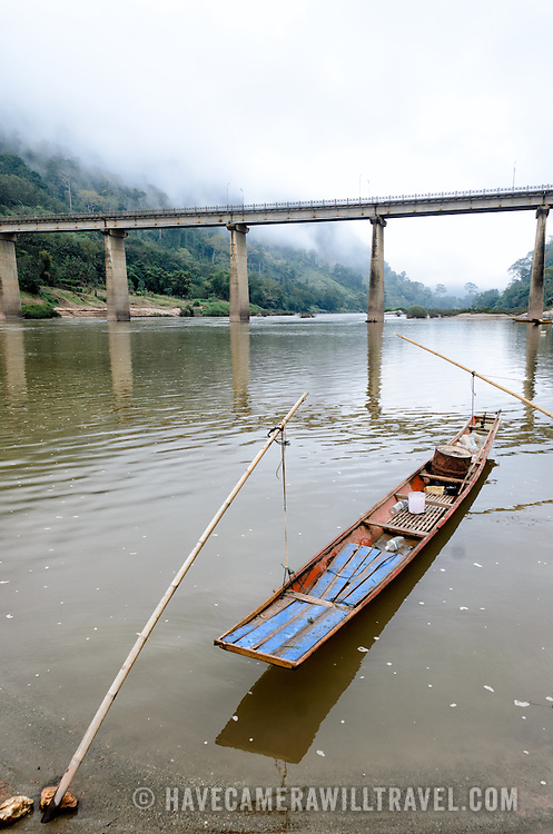 A wooden boat is moored by bamboo poles on the shore of the Nam Ou in Nong Khiaw in northern Laos.