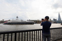 © Licensed to London News Pictures. 04/07/2018. London, UK.  A man takes a photograph as the new 243 feet long superyacht, Elandess arrives in London for the first time ever on the River Thames and moors at HMS President, the Royal Navy Reserve Unit next to St Katharine Docks and Tower Bridge this evening. Elandess was built at the Abeking and Rasmussen shipyard in Germany, launched in May 2018 and has just completed sea trials ahead of its London visit. Elandess has an axe-bow, dark hull and low-slung superstructure. There are a variety of entertaining communal spaces, from the 8 x 2.5-metre superyacht swimming pool located on the massive sun deck to the Nemo Lounge with portholes below the waterline and an observation lounge on the upper deck. Guest accommodation includes six staterooms, including the master suite which is placed forward on the main deck with an observation lounge directly above on the upper deck.  Photo credit: Vickie Flores/LNP