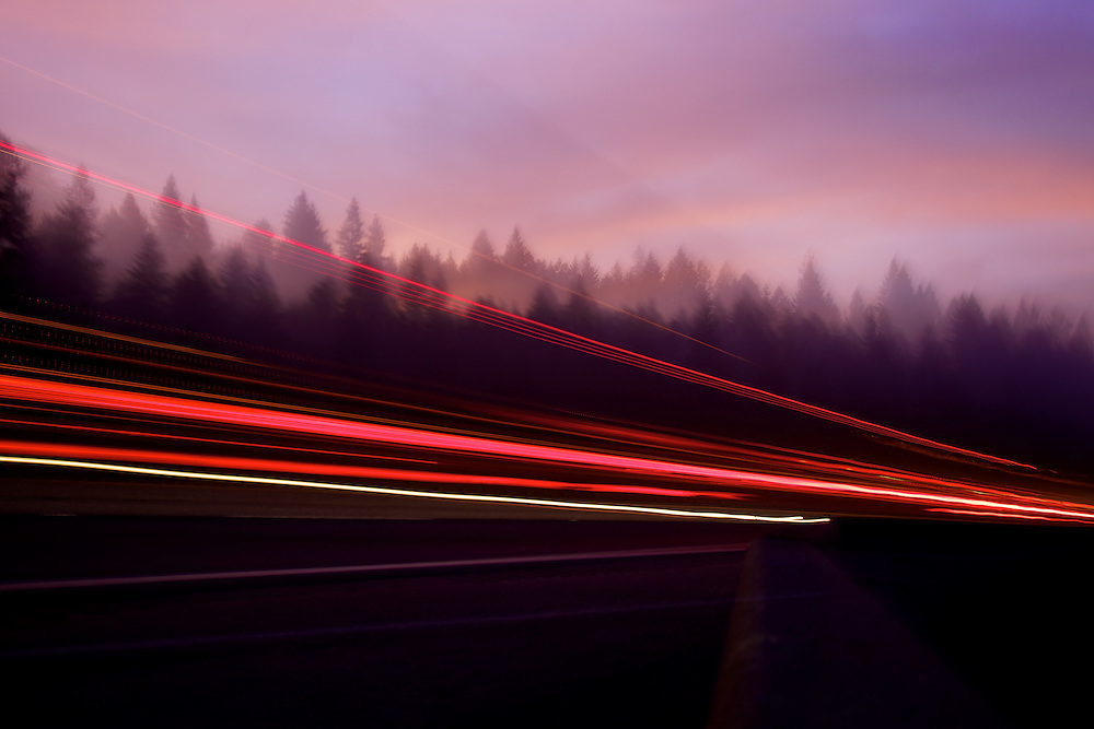 Trailing tail lights from vehicles traveling on Interstate-90 streak through early morning fog Wednesday as the glow of dawn silhouettes the tree line near Mullan Trail Road.