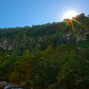 The sun sets over a cliff and river near Boquete, Panama.