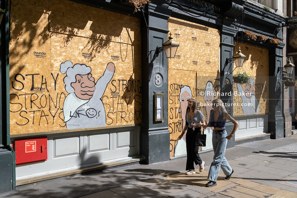 Two young women walk past a morale-boosting message written on plyboard of the boarded-up Garrick Arms pub on Charing Cross Road during the Coronavirus pandemic, on 20th August 2020, in London, England