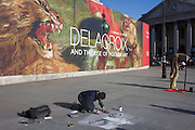 In front of the broad message on a hoarding announcing the next major exhibition by Delacroix at the National Gallery in London, a street artist draws a classical face on the pavement in Trafalgar Square.
