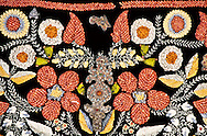 This coral Tuskiiz was made by Mariya Ilakova in 1913.  Its intricate design includes velvet, silk, coral, turquoise, cornelian, agate and embroididery.  It includes pieces of wedding jewelry that were sown into the textile after the marriage ceremony.  A Tuskiiz was made by the bride before the wedding and hung in an honorary place so the groom's relatives could appaise her skill.  Tuskiiz are used as wall decorations and to cover stacked futons.  Kasteyev museum of fine arts, Almaty