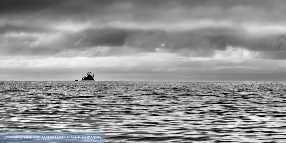 Silhouette of yacht at anchor close by Beehive Island, Kawau Island, Hauraki Gulf, New Zealand.