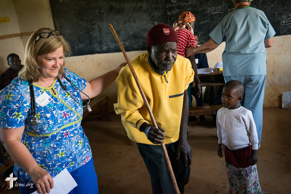 Nurse Janet Brown of Martinsville, Ind., attending Prince of Peace Lutheran Church, assists a patient toward a doctor at the Mercy Medical Team clinic Wednesday, June 11, 2014, at the Luanda Doho Primary School in Kakmega County, Kenya. LCMS Communications/Erik M. Lunsford