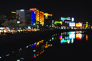 Neon signs illuminate the central business district located on the banks of the Naka River that runs through Fukuoka City, Japan.