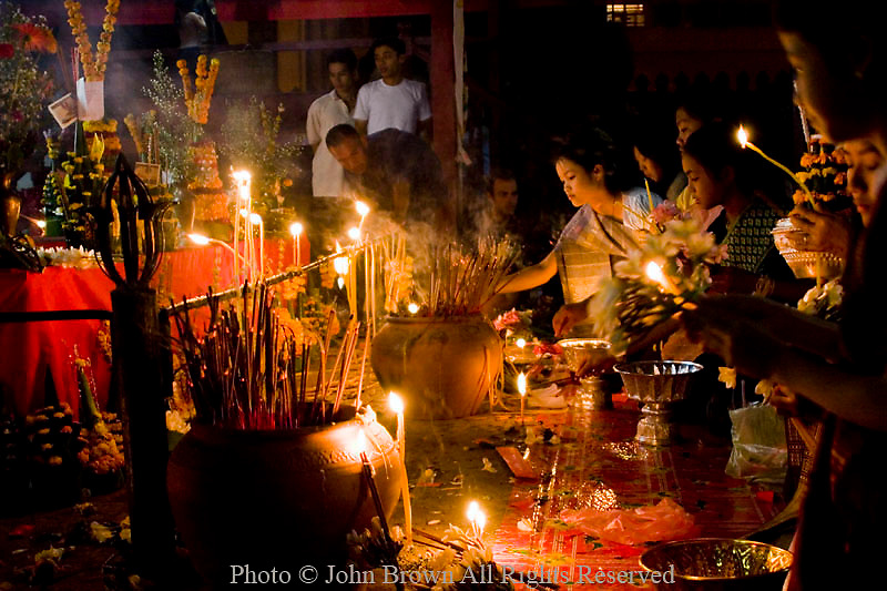 People are gathered with candles to pay tribute to the Pra Bang Buddha, displayed for 3 days each New Year at Wat Sawannaphumaham Temple in Luang Prabang, Laos. The streets of Luang Prabang are lined with tourists and locals alike as they enjoy the colorful display of traditional Lao culture that is on exhibit at this yearly event.  Luang Prabang is a UNESCO Heritage City and is known throughout Southeast Asia as one of its most cultural and scenic cities.
