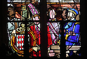 Stained glass window with Prince Rainier and Prince Albert of Monaco with their coat of arms, 1975, in the Grimaldi Chapel in the Basilica of Liesse Notre Dame, built 1134 in Flamboyant Gothic style by the Chevaliers d'Eppes, then rebuilt in 1384 and enlarged in 1480 and again in the 19th century, Liesse-Notre-Dame, Laon, Picardy, France. Pilgrims flock here to worship the Black Virgin, based on Ismeria, the Soudanese daughter of the sultan of Cairo El-Afdhal, who saved the lives of French knights during the Crusades, converted to christianity and married Robert d'Eppes, son of Guillaume II of France. Picture by Manuel Cohen